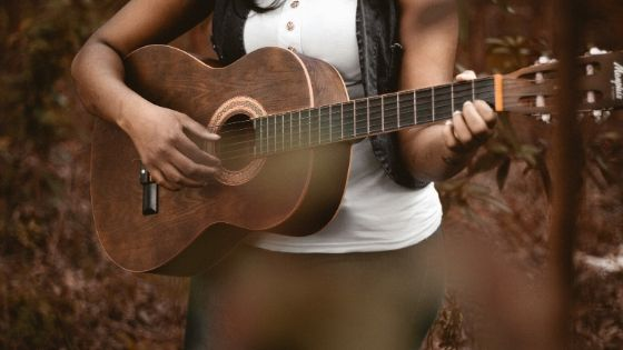 best way to record acoustic guitar at home - woman playing her acoustic guitar
