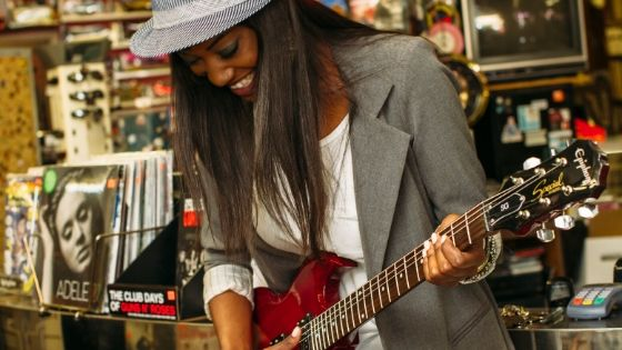 how to monetize a music blog - female musician playing guitar